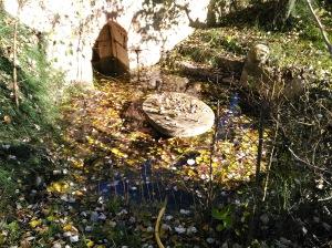 Zona de la fuente con asiento y mesa de piedra.